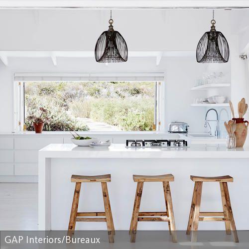Die Küche in Weiß erhält durch die modernen Pendelleuchten und die rustikalen Barhocker aus Holz einen charakteristischen Look. Die Kücheninsel wurde hier  …