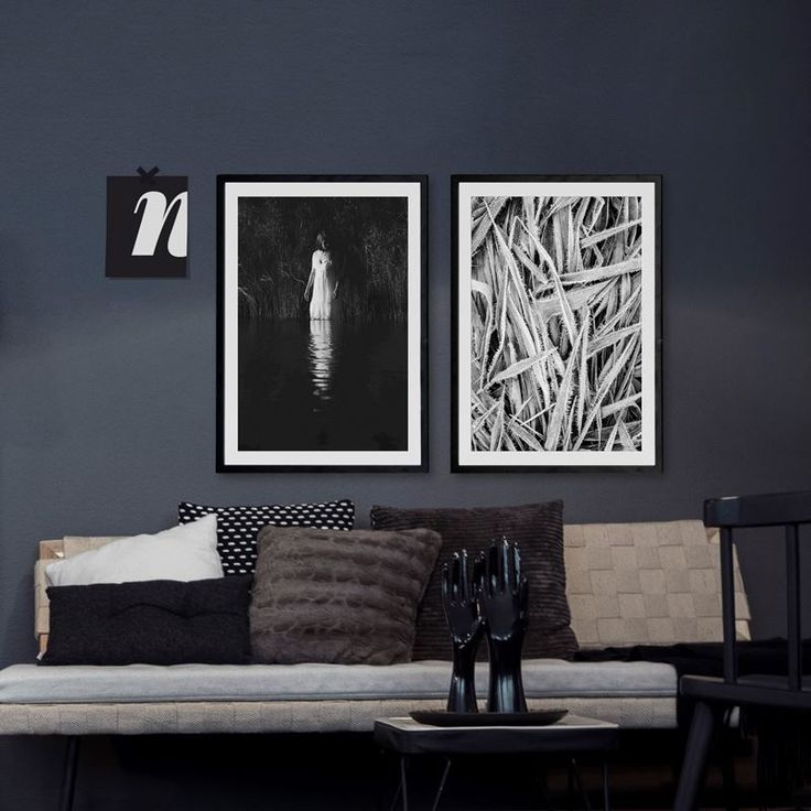 Dark walls in living room with black and white framed posters from printler.com, the marketplace for photo art. Motifs by Sandra Linnell and Erika Olofsson