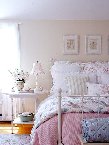 Layers of fluffy bedding make it impossible not to relax in this master bedroom. Quilts and a chenille duvet are the foundation for the bedding. Pillows with tiny floral prints or ruffled edges add to the sweet decor. The bedding is complemented by simple accents such as matted floral prints and a repurposed side table.