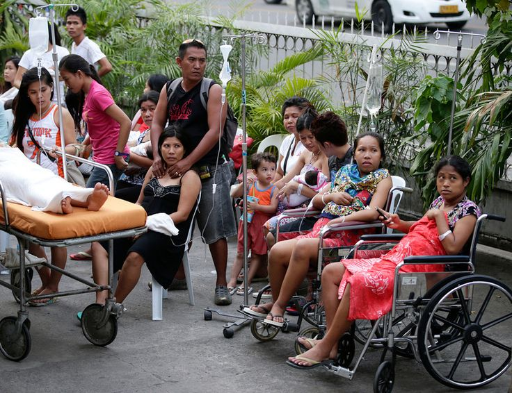 Patients stay outside a hospital to avoid aftershocks following a 7.2-magnitude earthquake that hit Cebu city in central Philippines Tuesday...