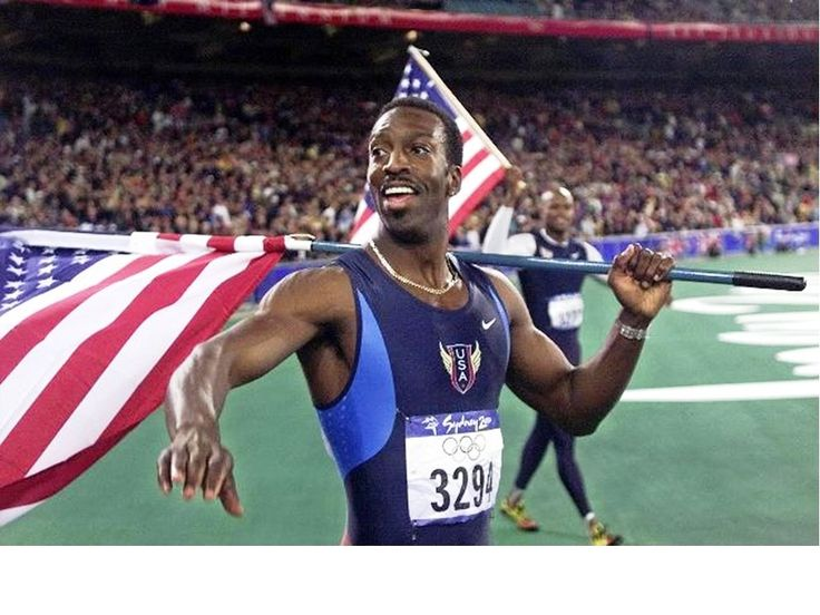 Athlete Michael Johnson of USA holding his national flag after winning the final of the Men's 400 metre sprint of Sydney Olympic Games at Stadium Australia, Homebush.