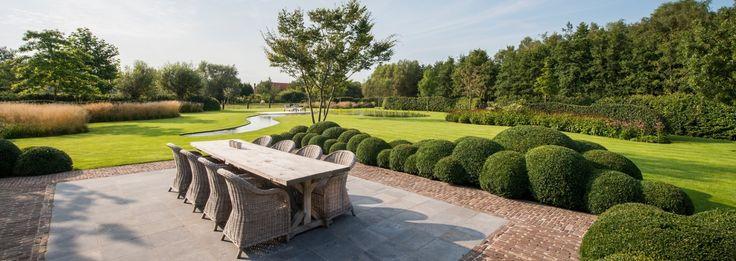 Landelijke tuin bij herbouwde hoeve met speelse vijver buxusbollen en siergrassen erg mooi - Hoe aangelegde tuin ...