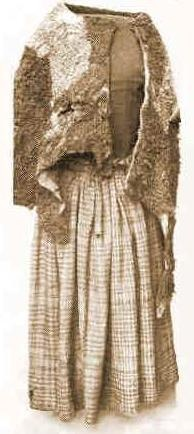 Woman's costume of Iron Age, discovered 1879. The Huldre Fen woman wore a lambskin cape next to the skin, and she wore another over the upper part of her body as an outer garment. A Tartan skirt was fastened to the body with a leather strap and a head-scarf or kerchief of the same material, fastened by a bird-bone pin, covered her head and neck.