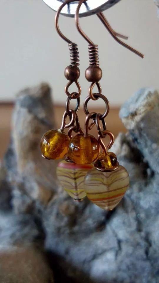 Koperen oorbellen gemaakt met glazen hartje en bruine glaskralen.