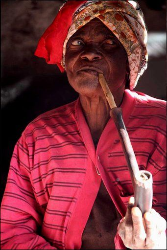 Xhosa woman smoking a traditional pipe.   Transkei, South Africa.