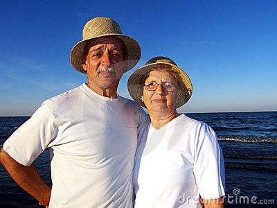 Senior couple with similar hats at sunset on the beach.