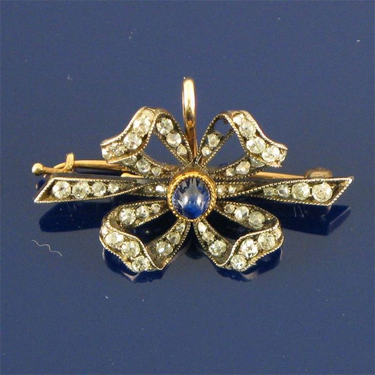 A Fabergé bow brooch set with a cabochon sapphire and small cushion and rose-cut diamonds in silver-topped gold. Workmaster Alfred Thielemann.