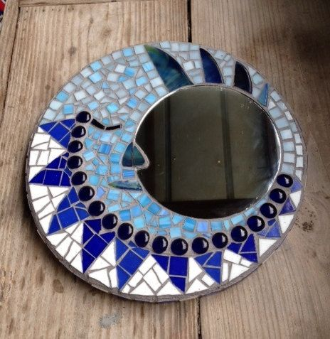 This one-of-a-kind stained glass mosaic piece measures 13 across with an off-set 7 mirror. The man in the moon design is made in various