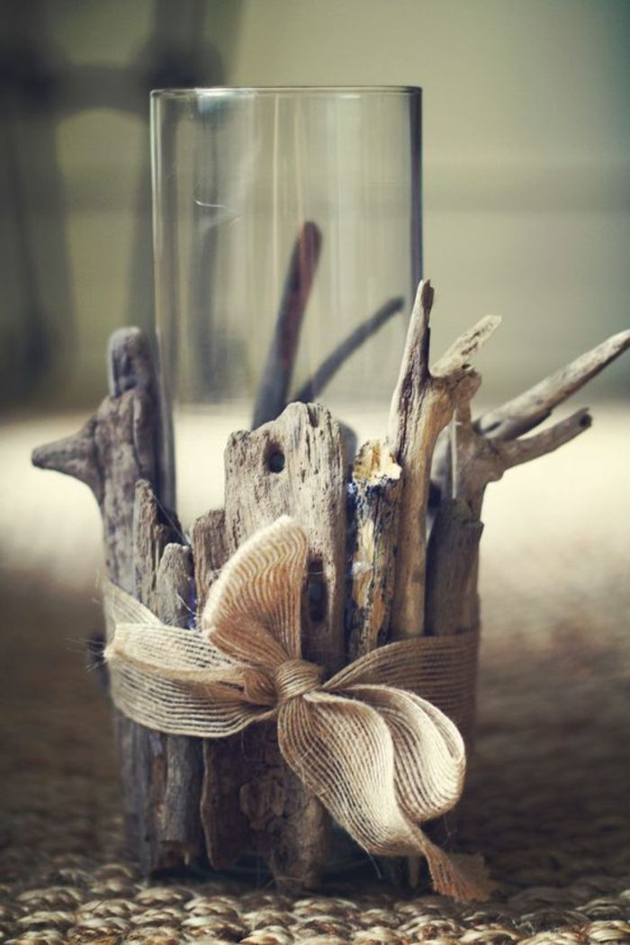 summer diys, clear tall glass, placed in holder made from asymmetrical pieces of driftwood, tied together with burlap bow