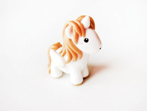 Cute and magical little pegasus pony miniature. It has a shiny gold mane and gold hooves.  The figure is completely handmade out of polymer clay, detailed with acrylic paints and finished with a glaze. It measures about 1.25 inches tall and 1 inch long.
