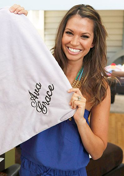 Melissa Rycroft holding up her embroidered blanket from Carousel Designs