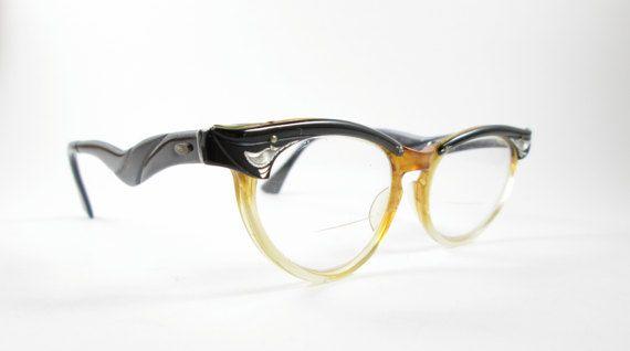 Bylite Vintage Cat Eye Brillenfassungen sind klar mit einem Hauch von Honig Gold dann in schwarz mit silbernen Decoarations auf jeder Seite vorne gekrönt. Dekorative schwarze Arme zu lesen: Bylite Alaun. 5 1/2 innen. Hier gezeigt mit Sehstärke, aber sie können leicht ersetzt werden, mit Ihren eigenen Sonnenbrille oder Linsen zu löschen. Einige allgemeine Abnutzung von Zeit und Nutzung sowie ein klein wenig anlaufen, das Metall in der Nähe von Schrauben und was aussieht wie ein Kratzer na...