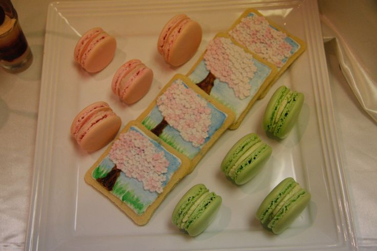 Hand-painted cookies with cherry blossoms and matching macarons.