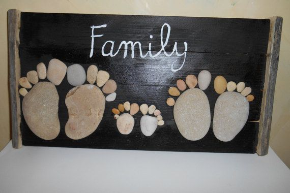 Dark solid wood panel wall appliques in the shape of a foot made with sea pebbles. inscription painted in oils and frame made with branches.