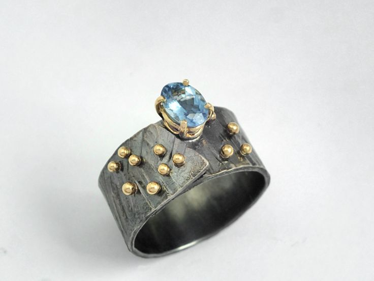 A wideband ring with oxidized sterling silver 18K studded gold granules and a…