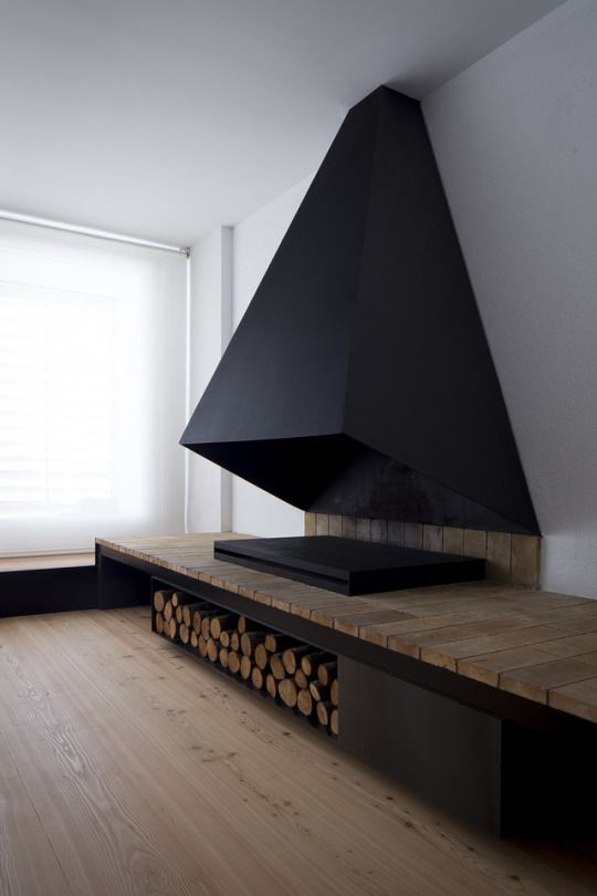 Matte black smoke hood for flat surface fireplace. Wood storage underneath.