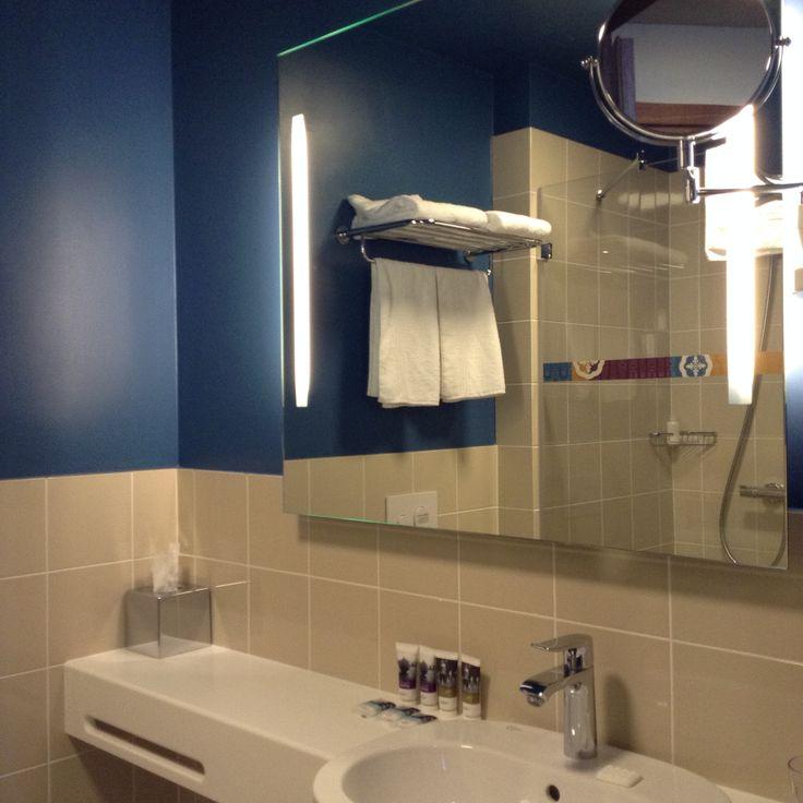 Mercure Hotel Riga bagno minimalista con pareti in resina blu oceano e rivestimento chiaro di piastrelle.