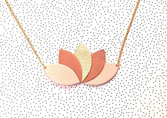 Collier cuir chaîne en laiton doré, de qualité, fine et délicate, à maillons plats, coloris champagne.  Motif composé de 5 pièces de cuir forme feuille, pétale, navette assorties dans des tons nude de rose et doré.  Rose pâle, pastel, beige rosé, irisé et or.  Fermoir mousqueton et chaînette dextension.  Original de par sa forme et sa matière, classique et chic grâce à ses délicats coloris, ce collier accessoirisera facilement vos tenues aussi bien en journée quen soirée.  Avec ses coloris…