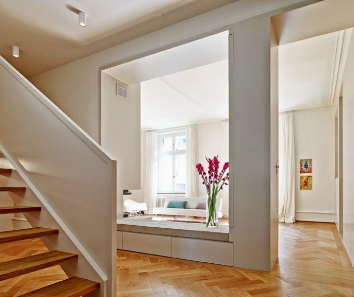 Der neue Durchbruch zwischen Wohnraum und Korridor wird ummantelt von Schreinerarbeiten, die Stauraum bieten, wie Schubladen unter der Bank und einer …