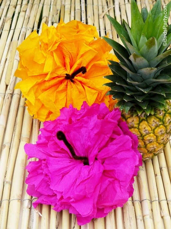 "They are sooo easy to make - Just make a paper pom like you would normally (tutorial here), then twist a piece of brown pipe cleaner around the center of each open pom, and open the pom flat, scrunching some of the ""petals"" to give it the Hibiscus look."