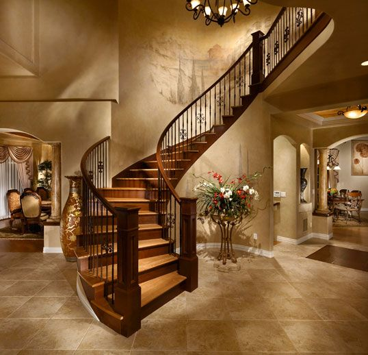 Dramatic foyer with sweeping curved staircase to the gourmet kitchen
