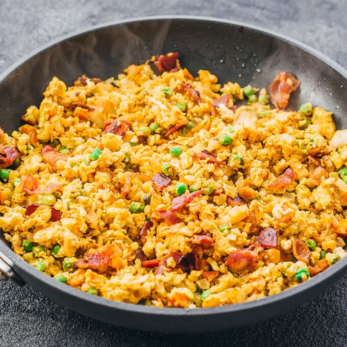 Easy and simple cauliflower fried rice stir fry with egg, bacon, and kimchi in a black pan