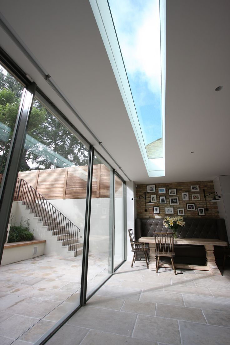 Love the flow of the floor from house into garden. Minimal Windows along a rear extension with walk-on rooflight to the balcony above.