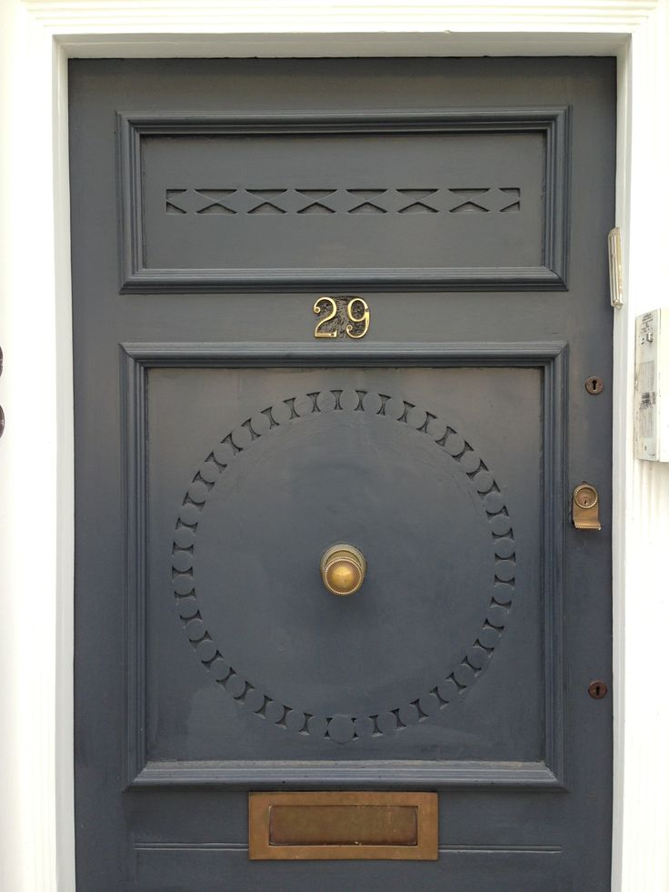 Slate grey painted Georgian timber door with brass door furniture on Conway Street, London W1.