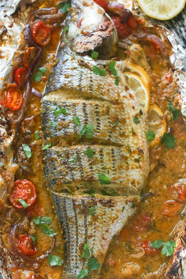 Whole baked Seabass  with tomatoes , onions, garlic herbs and spices