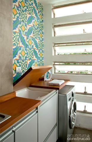 A bancada de peroba da cozinha se abre e revela um tanque, com torneira escondida na lateral interna. Ao lado, vem a lava e seca.