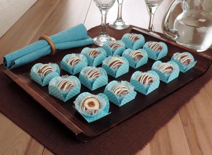 docinho de leite em pó trufado com cobertura de chocolate, várias unidades dispostas regularmente em forminhas de papel azul sob uma tábua de madeira
