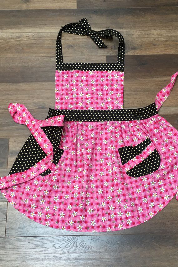 Two aprons in one - reversible! Hot! Hot! Hot pink and polka dots! Hot pink gingham is sprinkled with bumblebees on this beautiful retro apron. The polka dot waistband makes your waist appear hourglass tiny! All the ties are long enough to tie in the front, back or as pretty bows on the side. The sassy little skirt is softly curved. Two pretty polka dot pockets are lined and trimmed in bumblebees on pink gingham. Very cute! Absolutely reversible, turn the apron around and wear black and…