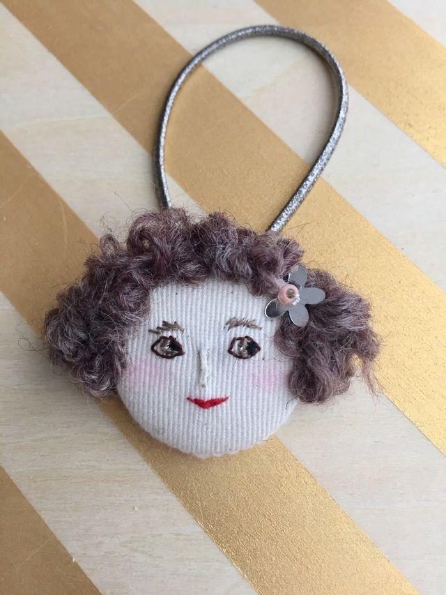 女の子の顔刺繍をしたヘアゴムです。 娘の髪にお人形がついていたらかわいいかな…と思い作り始めたお品です。ヘアゴムとしてはもちろん、結びつけてバッグチャームや帯留めなどにも。 くるみボタンベースになっています。 素材 コットン、ウール毛糸、ビーズ、レー...