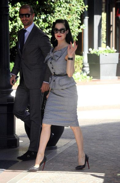 Dita Von Teese Skirt Suit     There isn't a moment when Dita Von Teese isn't looking impeccably styled! The burlesque queen donned a retro gray skirt suit with a playful bow. The glam starlet stepped out in spiked Louboutin pumps and her signature red lips.   Brand: Christian Dior