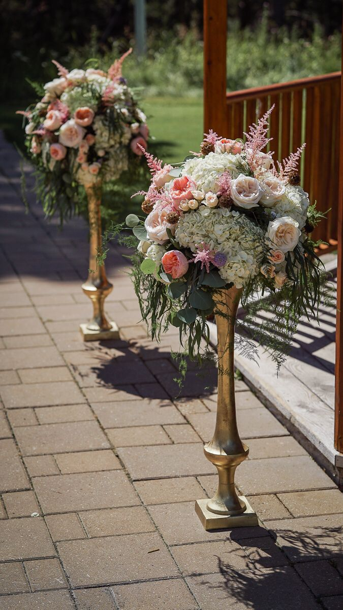 Gold Roma vases with white hydrangea, Juliet & White O'Hara garden roses, astilbe, scabiosa & wispy foliage for an August wedding at Silvertip Resort in Canmore, Alberta. Floral design: Flowers by Janie www.flowersbyjanie.com