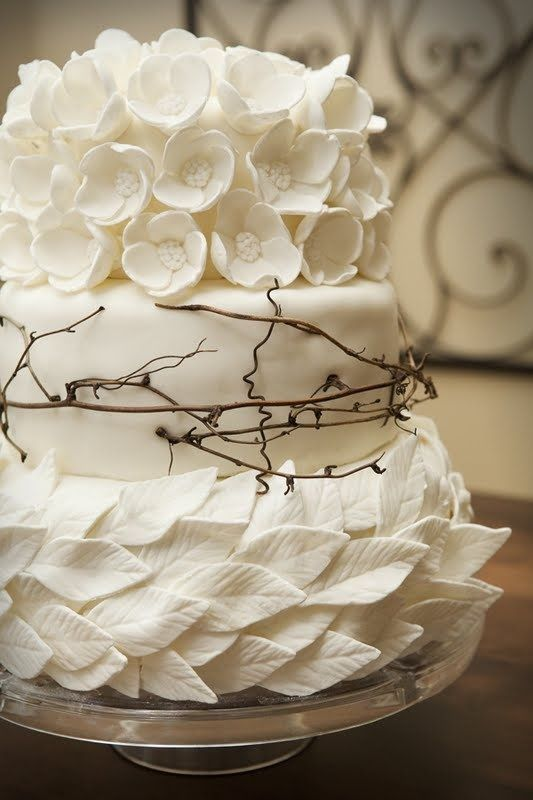 Beautiful white wedding cake with rustic floral and leaves fondant details.