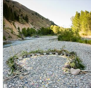"""Another key element was the """"sacred circle,"""" a circle on the ground made of stones, wood, and greenery, where the couple exchanged vows. The circle functioned like an altar, expressing  Megan and Casey's spirituality and their desire for a c..."""