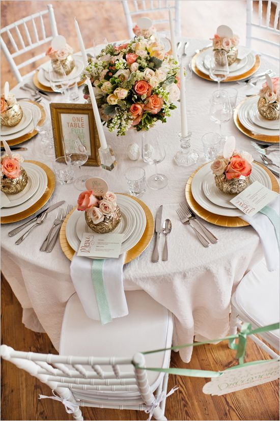 Elegant gold table setting. Possible decor with pearls, champagne. Gift box topped with a flower sitting on plates.