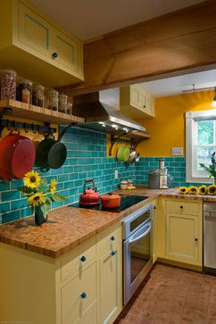 Love the colors (yellow cabinets + butcher block-style counters + turquoise accents)...the subway tile backsplash not so much