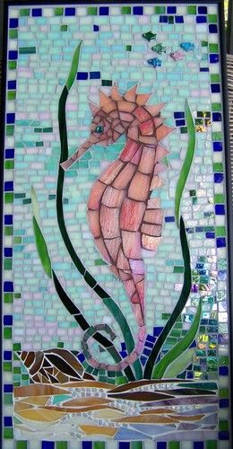 Interest is added to this piece with the use of iridized glass and beads which create a light catching shimmer and fantasy to the undersea world. Three colors of sanded grout were used to finish the piece. It is framed with a flat black metal frame by Marie Groves