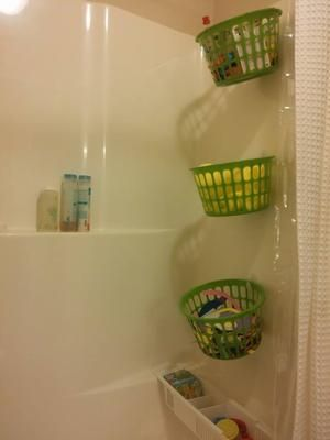Dollar store bathtub storage solution -- dollar store baskets plus command hooks. Perfect for holding bath toys or really just about anything {featured on Home Storage Solutions 101}