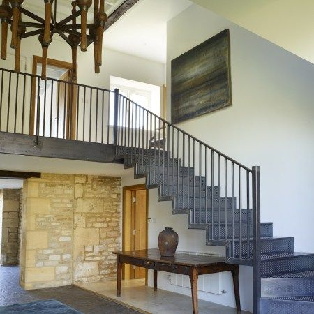 A blue steel staircase and balustrade have been fashioned as if by a local blacksmith. Design by Pippa Paton Designs.