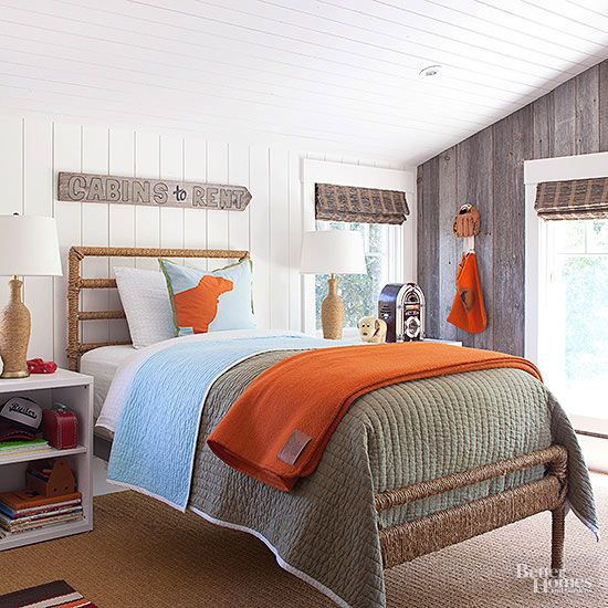 A rope-wrapped bed frame and matching lamps add texture to this cabin-inspired bedroom. Quirky antique accessories, including a jukebox radio and wooden camp sign, stand out against shiplap and recycled barnwood walls. /