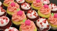 Mini bolinhos de baunilha com creme de chocolate rosa, decorado com UMA rosinha cor de rosa.  O Outro sabor e o mini-veludo vermelho com marshmallow e coraçõeszinhos micro vermelho e rosa.