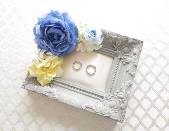 """【全国一律送料500円キャンペーン実施中】アンティーク調の彫刻が美しい枠の内部分がクッショントレーになってリングが置ける、""""フレームトレー型リングピロー""""です。結婚式後は無くしがちな指輪の指定席として、また玄関に置いて鍵や腕時計置きなどのアクセサリー置きとしてずっと使うことができます。----------------------------------------------- <商品の仕様>フレームサイズ:縦20.5×横17×奥行3.5cm クッション面:縦12×横7.5cm 素材:アーティシャルフラワー、フレーム=木-----------------------------------------------●ご注意・使用しているフレームはアンティーク仕上げのため塗装ムラがあることがございます。予めご了承いただきますようお願い申し上げます。…"""