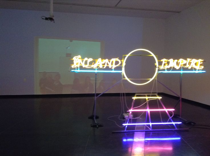 Untitled (blue wall, projection, people, the gap and another artwork) (2015) by Paul Bai, live feed video projection with Inland Empire (2008) by Janet Burchill and Jennifer McCamley, dimensions variable