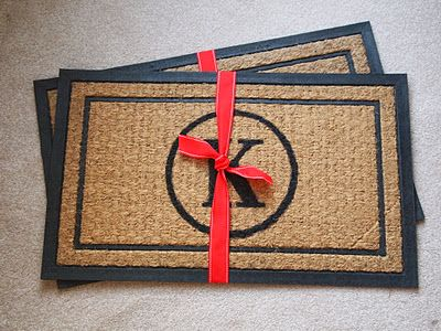 Make a personalized door mat for only $7 (basic mat comes from Walmart and use craft paint to personalize).  Would have to put it somewhere not exposed to weather elements I imagine...