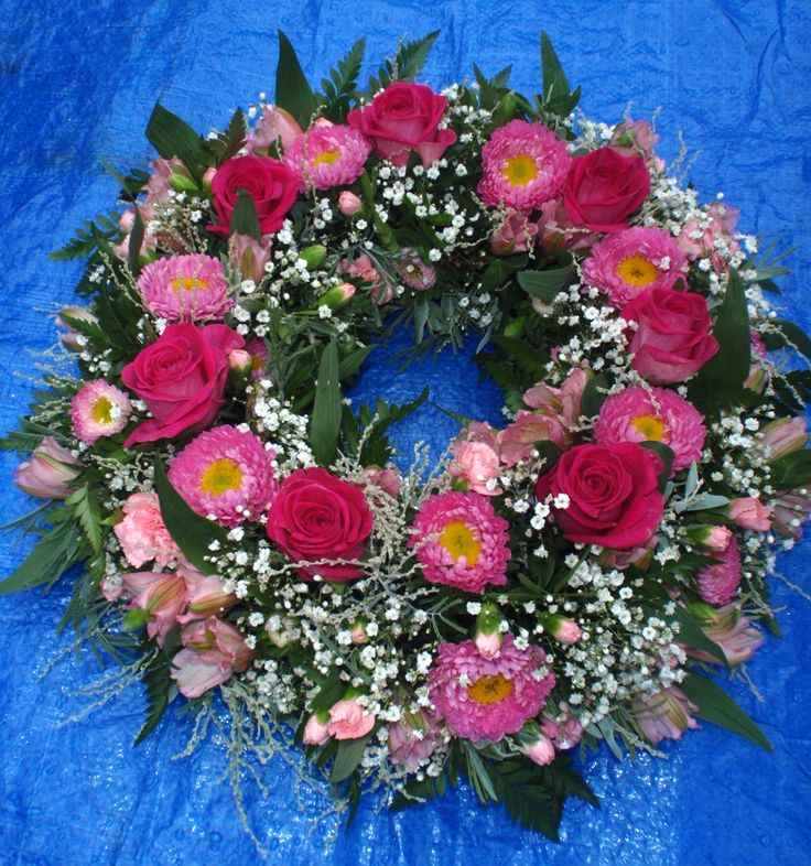 All pink wreath using roses, spray carnations, alstromeria, callistephus, and white gypsophila.