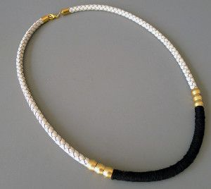 With this Sophisticated Leather Cord Necklace on, you will not only look stylish, but polished as well. This free DIY jewelry tutorial shows you how to make a necklace with a white leather cord and some black thread. As an added bonus, it also demonstrates how to add some glamorous gold to your necklace as well.