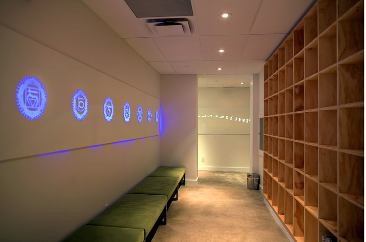 Chopra Yoga Centre in Toronto by Prototype Design Lab. Back-CNC cut chakra symbols in corian are illuminated by a colour-changing LED light along the storage hallway of tongue-in-groove birch storage cubbies.
